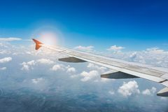 Wing of the plane on blue sky with sunlight. travel concept Stock Images
