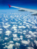 Wing of a plane and clouds Stock Photo