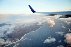 Wing of the plane over coastline. Wing of the plane flying above beautiful coastline (aerial view Royalty Free Stock Photos