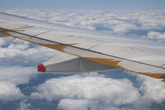 Wing of a plane over lots of white beautiful clouds Stock Photo