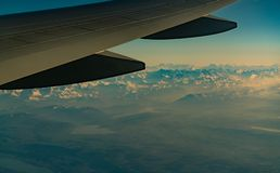 Wing of plane over mountain cover with white snow. Airplane flying on blue sky. Scenic view from airplane window. Commercial. Airline flight. Plane wing. Flight stock photos