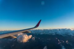 Wing of the plane on sky background. plane wing with cloud patterns. view from the window of a plane of the wing and blue sky back Royalty Free Stock Photography