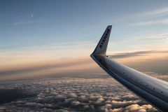 A wing of a Ryanair plane landing at sunset stock photos