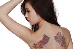 Wing Tattoos. Brunette woman with wing tattoos on her back. Professional make-up artist Stock Photo