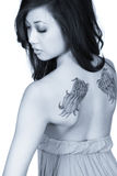 Wing tattoos. Slightly blue toned image of a beautiful Asian woman showing the wing tattoos on her back. Professional make-up artist Stock Photos