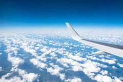 Wing view of the airplane on a winglets and jet engine, fluffy clouds on the skyline during climbing flight level. Stock Image