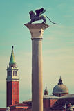 Winged lion on marble column in Venice, Italy. Bronze sculpture of winged lion on column as San Giorgio Maggiore church on background in Venice, Italy (toned Stock Image