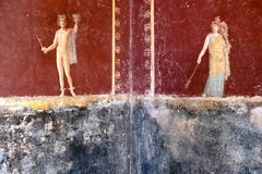 Winged Amorino of the same Erote on a white wall. Perseus fresco with wings on his feet showing the head of Medusa, in a Domus of Pompeii, the ancient Roman city royalty free stock photos