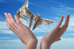Winged Escape. Two hands reaching for dollar bills shaped like butterflies. A blue sky serves as the backdrop royalty free stock photography