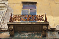 Winged female figure. Rusty floral pattern and swans on balcony balustrade of abandoned neoclassical house. Athens Greece Stock Photo