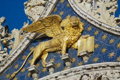 Winged golden lion decorating upper facade of the Saint Mark`s Basilica in Venice, Italy. stock images