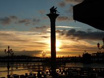Venice Sunset over Winged Lion of St. Mark. Marble column with Winged Lion of St. Mark at sunset.  Outdoor cafe can be seen in the foreground Royalty Free Stock Photos