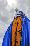 A Winged Moko-Jumbie or Stiltwaker at the Queen`s Park Savannah in Port-of-Spain. A blue-winged masquerader stands quietly on his stilts preparing himself Stock Photo