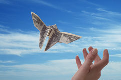 Winged Money. A hand trying to catch a dollar bill shaped like butterflies. A blue sky serves as the background royalty free stock photos