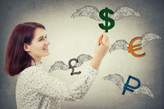 Winged money signs. Young businesswoman holding a pencil in her hand, drawing winged money signs, as dollar, euro, pound and ruble are flying away  on gray wall Stock Photography