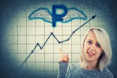 Winged ruble. Young businesswoman, with a happy emotion, showing with her hand to a winged russian ruble sign and a rising graph. Concept of financial analysing stock image
