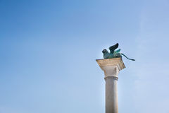 Winged St. Mark Lion statue on a column, copy space on blue sky background Stock Photo