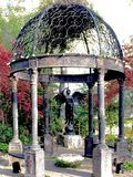 Winged Statue at the Gazebo. Winged metal statue blowing her trumpet surrounded by trees & a metal gazebo Royalty Free Stock Photography