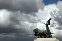 Winged victory. Statue on top of the Vittoriano with winged victory on chariot and dark clouds in the background Royalty Free Stock Photos