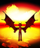 The Wings Of Evil. Devil with outstretched wings flying in a sunset sky Royalty Free Stock Photos