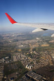 Wings over city. Wings of a public airplane  over the city Royalty Free Stock Photo