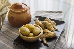 Wings and potato with clay pot on table Stock Image