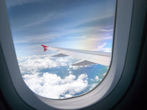 Wings and sky. Clouds and sky as seen through window of an aircraft Stock Photography