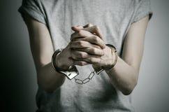 Więźniarski i skazujący temat: mężczyzna z kajdankami na jego rękach w szarej koszulce na szarym tle w studiu, stawia kajdanki da Obraz Royalty Free