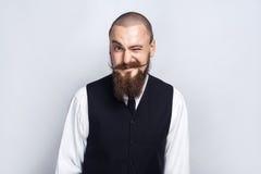 wink Hübscher Geschäftsmann mit dem Bart- und Lenkstangenschnurrbart, der Kamera und das Blinzeln betrachtet Stockfotografie