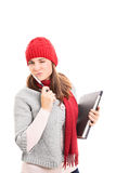 Wink. Portrait of a beautiful young woman winking, holding a pen, book and a notebook, wearing winter clothes isolated on white background Stock Image