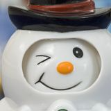 Wink snowman square. Close-up of a winter season table scene tabletop of a blue tablecloth against a white background with colorful colourful plastic winking stock photos