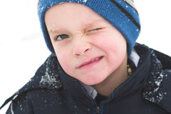 Wink wink. A child winks while playing in the snow stock image