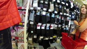 In winkel kiest de vrouw de sokken en de legging van mannen stock video