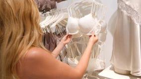 Winkel van vrouwen` s ondergoed Vrouwen` s damesslipjes op hangers in een geslachtsopslag, 4k, langzame motie stock footage