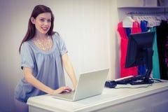 Winkelarbeider die laptop met behulp van door tot stock afbeeldingen