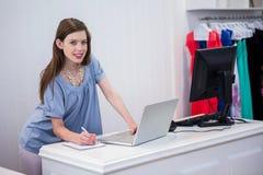 Winkelarbeider die laptop met behulp van door tot royalty-vrije stock fotografie