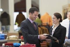 Winkelbediende Assisting Businessman stock foto's