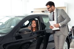 Winkelbediende bij de verkopende voertuigen van het autohandel drijven royalty-vrije stock fotografie