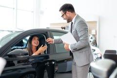 Winkelbediende bij de verkopende voertuigen van het autohandel drijven royalty-vrije stock afbeelding