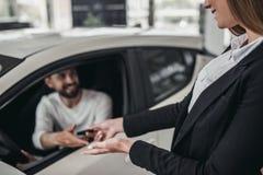 Winkelbediende met klant in het autohandel drijven stock afbeelding