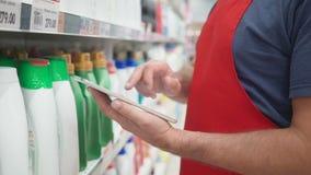 Winkelbediendehanden die PC-tablet voor reinigingsmachinesplanken gebruiken in moderne kruidenierswinkeldetailhandel stock videobeelden