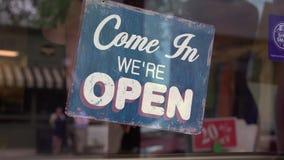 Winkeleigenaar die een open teken over wegknippen