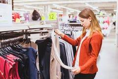 Winkelen, vrouw die kleren kiezen stock afbeeldingen