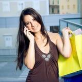 Winkelend meisje met mobiele telefoon stock afbeelding