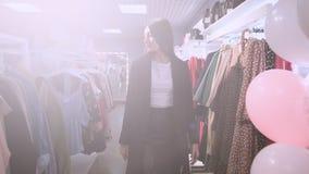 Winkelend meisje Portret van een mooie vrouw in de klerenopslag Jong aantrekkelijk donkerbruin oostelijk meisje in kleding stock video