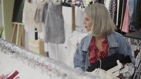 Winkelend meisje Portret van een mooie vrouw in de klerenopslag Jong blondemeisje met rode lippen in een kledingsopslag stock videobeelden