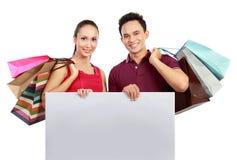 Winkelend paar met lege raad Stock Fotografie
