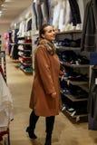 Winkelende Glimlachende vrouw in kledingsopslag het winkelen Royalty-vrije Stock Afbeeldingen
