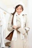 Winkelende vrouw die de winterhandschoenen probeert Royalty-vrije Stock Afbeelding