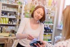 Winkelende vrouw die met creditcard betalen stock fotografie